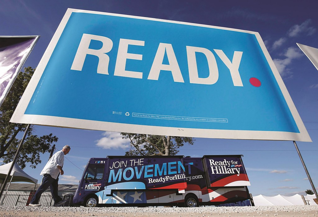 A man walks by a bus supporting former Secretary of State Hillary Clinton at the location for Senator Tom Harkin's 37th Steak Fry in Indianola, Iowa. (REUTERS/Jim Young)