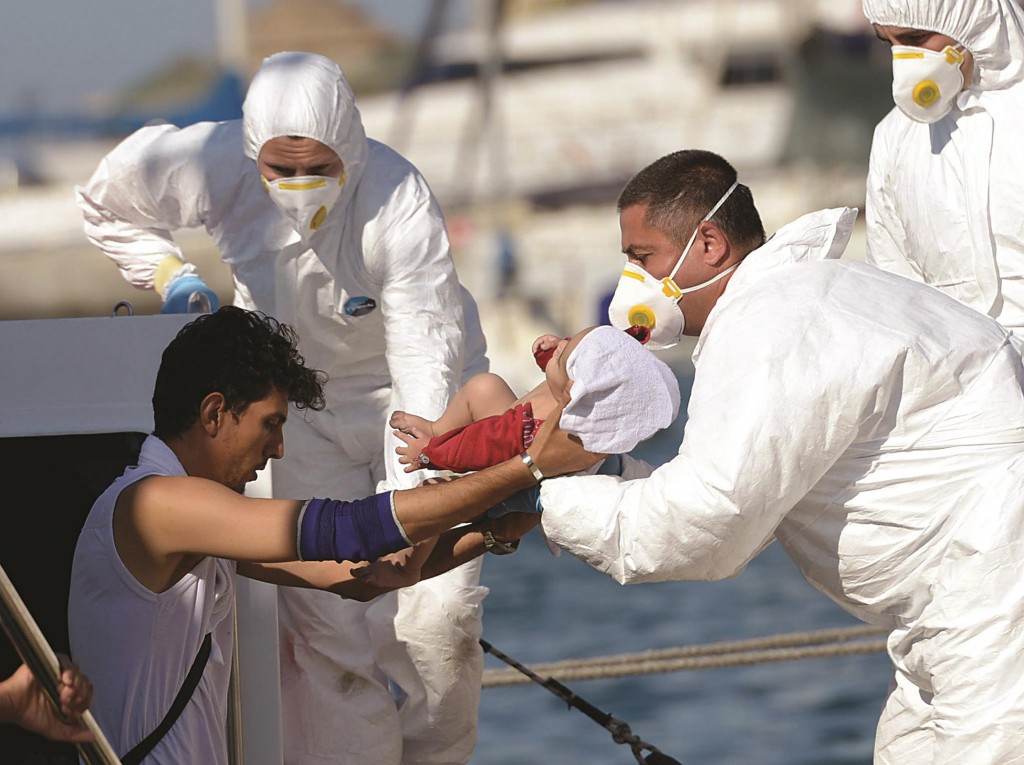 A migrant disembarks with his baby from a boat of the Armed Forces of Malta (AMF) after arriving at the Haywharf maritime base, in Floriana, Malta, in this recent photo. The migrants form part of a group of 250 who were picked up by a cargo ship from a sinking boat.  (Matthew Mirabelli/AFP/Getty Images)