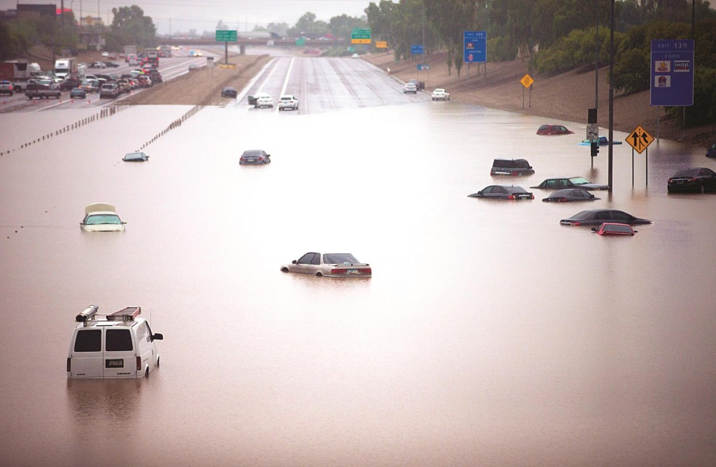 Cars are stuck in flood waters on I-10 east at 43rd Ave. after heavy storms pounded the Phoenix area early Monday, flooding major freeways, prompting several water rescues and setting an all-time single-day record for rainfall in the desert city. (AP Photo/The Arizona Republic, Michael Chow)