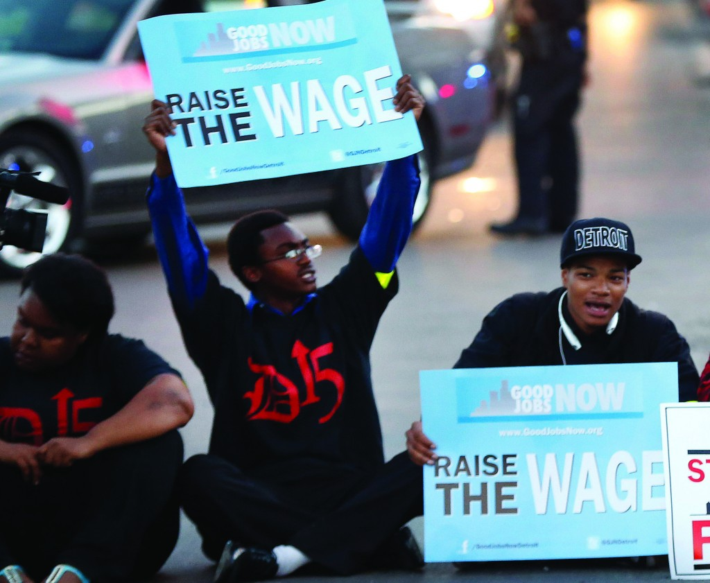 Protesters block traffic on Mack Avenue in Detroit as part of a national protest to push fast-food chains to pay their employees at least $15 an hour Thursday. (AP Photo/Paul Sancya)