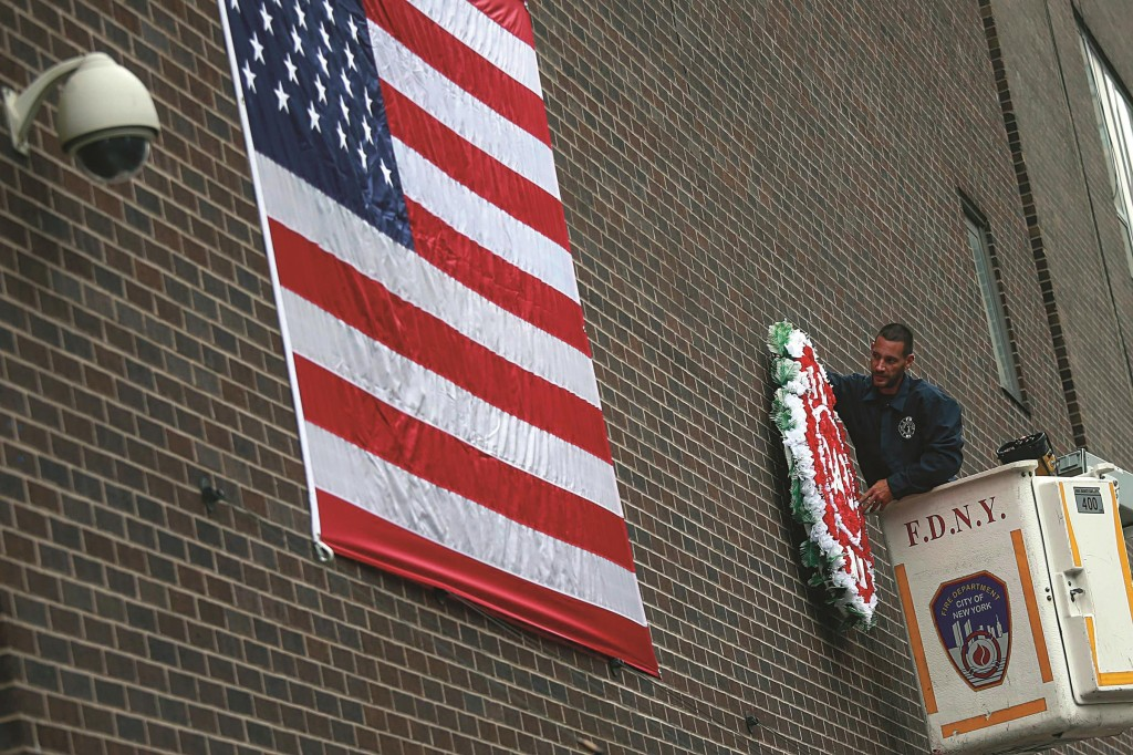 A firefighter on Tuesday hangs a U.S. flag and wreath on an outside wall of Engine Company 10, located across from the World Trade Center site. (Reuters/Adrees Latif)