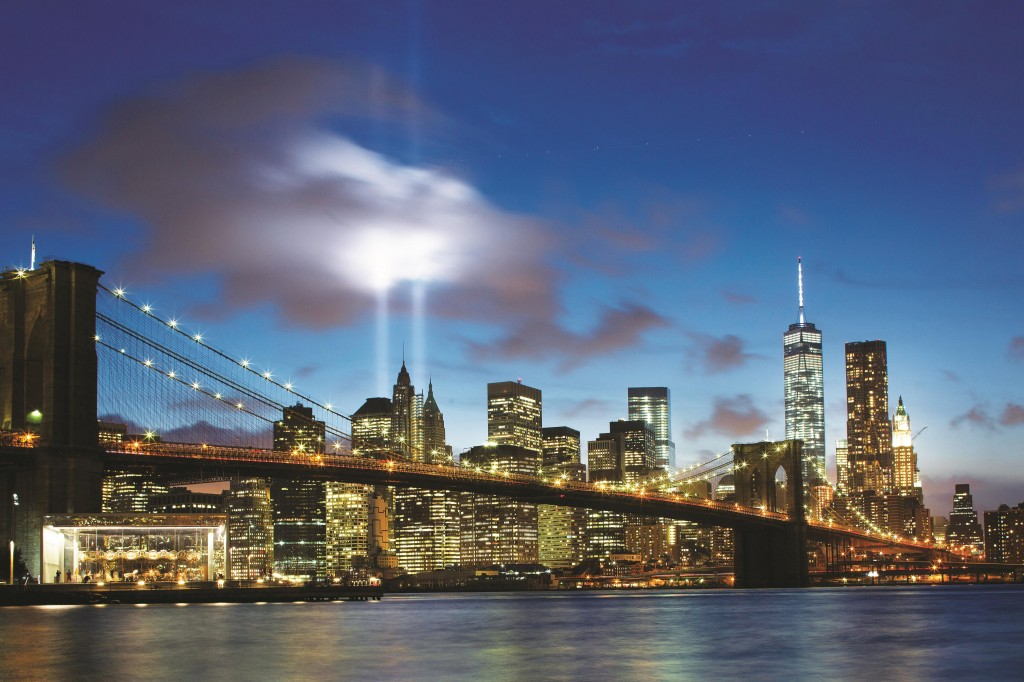 The Tribute in Light on Wednesday rises behind the Brooklyn Bridge and the World Trade Center complex on the eve of the anniversary of the  Sept. 11, 2001, attacks. (AP Photo/Mark Lennihan)