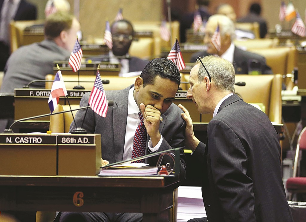 Assemblyman Nelson Castro (L) in the Assembly Chamber before he resigned last year. (AP Photo/Mike Groll)