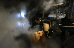 Jose Garcia catches a barrel as it moves through a steam line, which softens the wood, at McGinnis Wood Products in Cuba, Mo., on Friday, Sept. 5, 2014. Steam makes the white oak pliable, ready to shape as a 53-gallon spirit barrel. (Robert Cohen/St. Louis Post-Dispatch/MCT)
