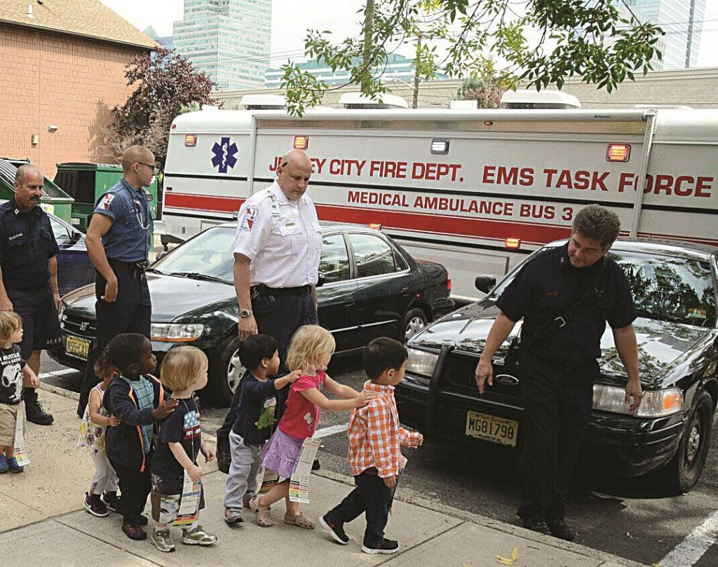 Children from the Growing Tree Learning Center II on Thursday are led to an EMT bus to be tested at the Jersey City Medical Center. (AP Photo/The Jersey Journal, Joe Shine)