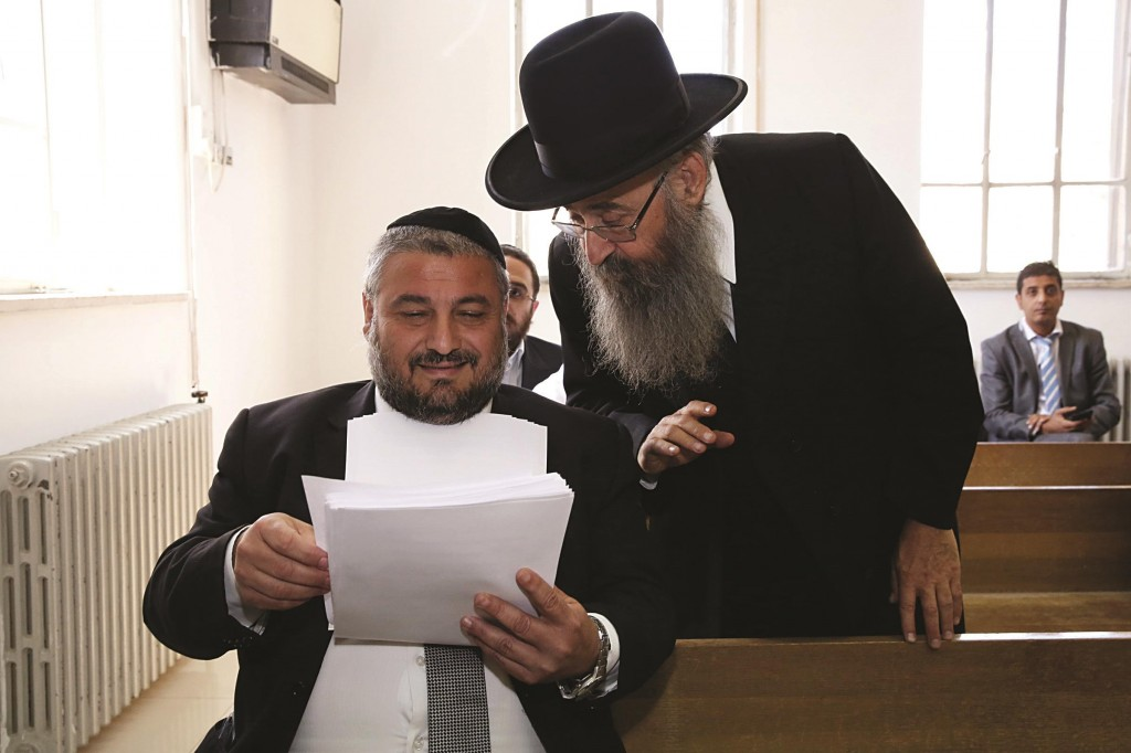 Beit Shemesh mayor Moshe Abutbul (seated, foreground) seen speaking to Rabbi Avraham Yosef Leizerson, Chairman of Chinuch Atzmai, in the District Court  in Yerushalayim on Sunday. (Flash90)