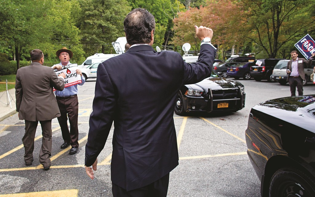 Gov. Andrew Cuomo on Tuesday waves to anti-fracking protesters as he arrives to cast a vote Tuesday in Mount Kisco. (AP Photo/Craig Ruttle)