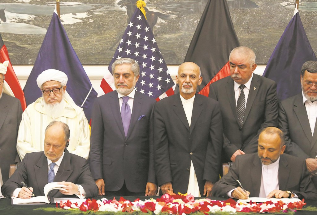 Afghanistan's national security adviser Mohmmad Hanif Atmar, seated at right, and U.S. Ambassador James Cunningham, left, sign the documents of the Bilateral Security Agreement (BSA) at the presidential palace as Afghanistan's president Ashraf Ghani Ahmadzai, center right, and chief executive Abdullah Abdullah, center left, watch, in Kabul, Afghanistan, Tuesday. (AP Photo/Massoud Hossaini)