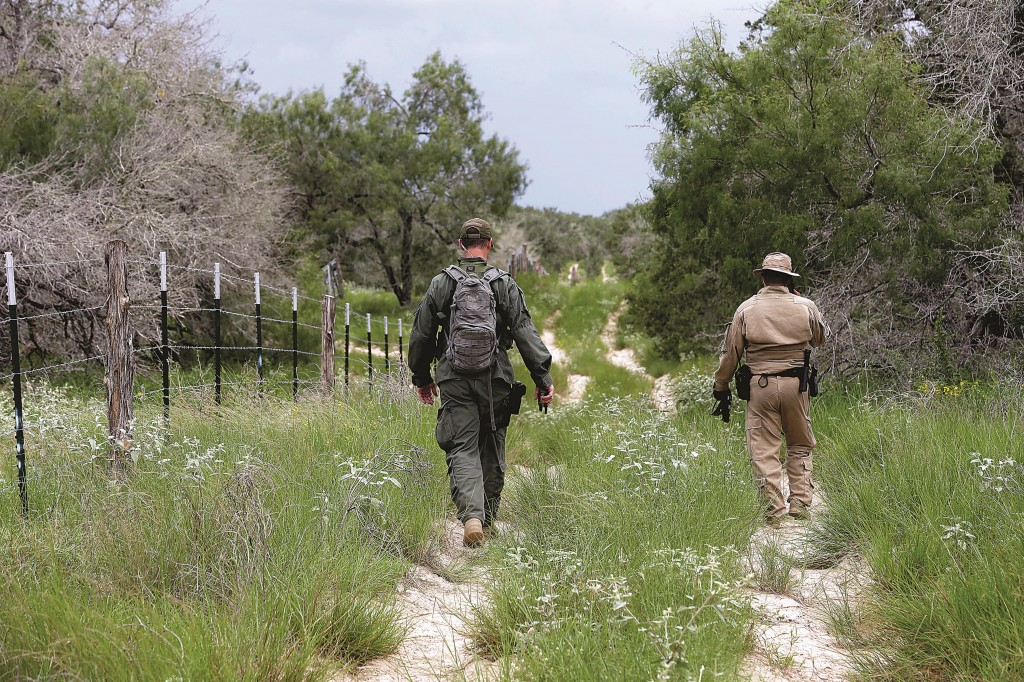 A U.S. Border Patrol Search, Trauma, and Rescue (BORSTAR) agent and Air and Marine agent look for signs along trail while on patrol near the Texas-Mexico border, Friday, near McAllen, Texas. (AP Photo/Eric Gay)