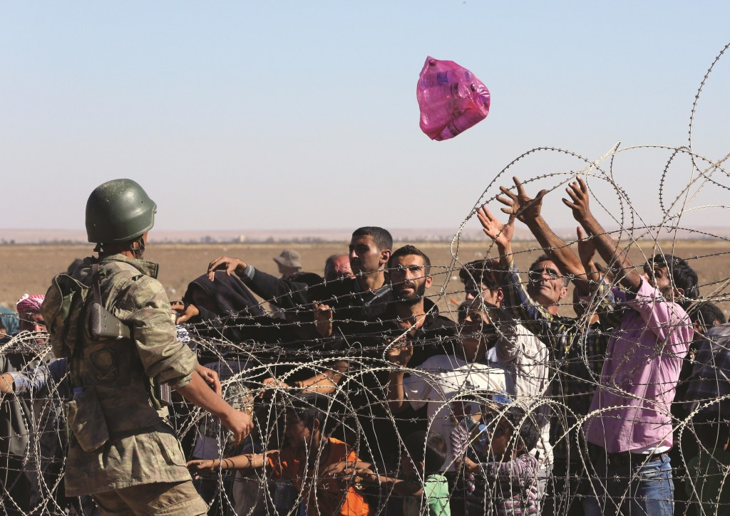 A Turkish soldier throws a pack of water toward the Syrian refugees who were waiting at the border in Suruc, Turkey, on Sunday.  (AP Photo/Burhan Ozbilici)