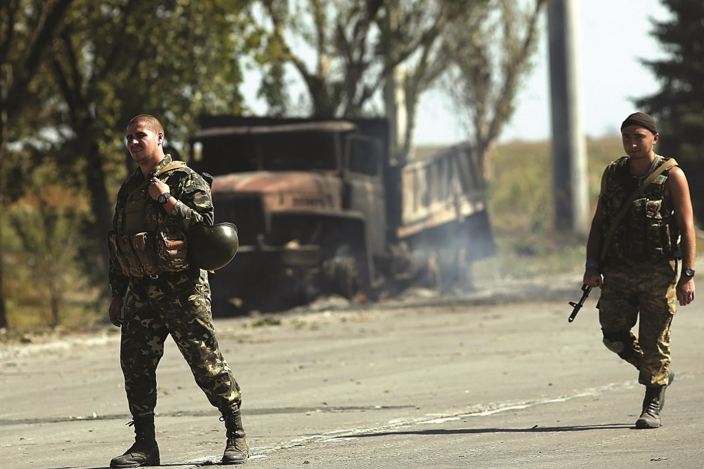 Ukrainian soldiers stand near a frontline position beside a burning truck on the outskirts of the strategic coastal city of Mariupol, following an evening of heavy shelling by Russian-backed separatists on Sunday Mariupol, Ukraine.  (Spencer Platt/Getty Images0)