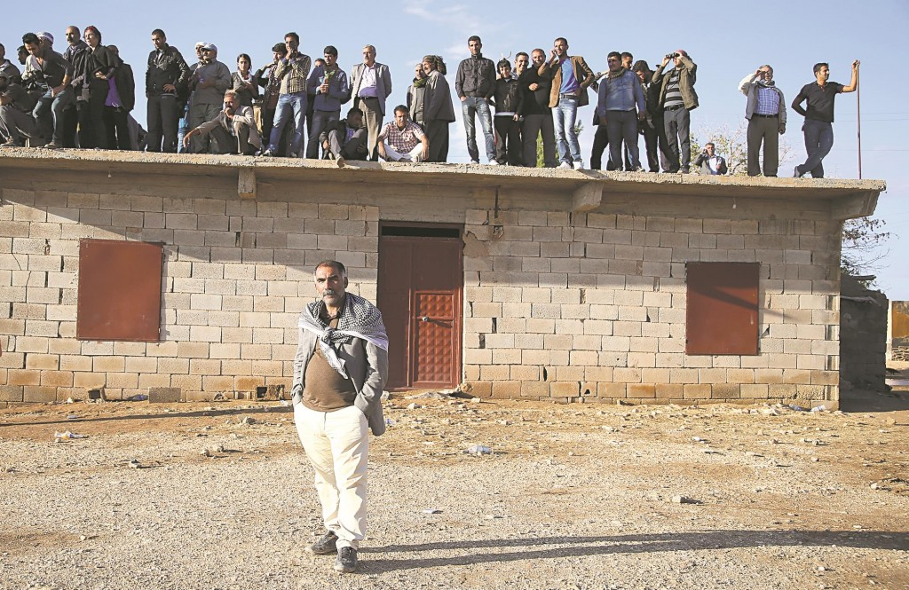 Residents in the border village of Alizar keep guard, Monday, waiting in fear from Islamic State mortars, fired as it tightened its siege of the strategic town of Kobani, on Syria's border with Turkey.  (Stringer/Getty Images)