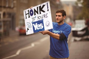 David Aguilar from Catalonia, who is visiting Scotland to support the Scottish independence referendum, holds up a placard supporting a Yes vote at passing motorists in Edinburgh, Scotland, Thursday. (AP Photo/Matt Dunham)