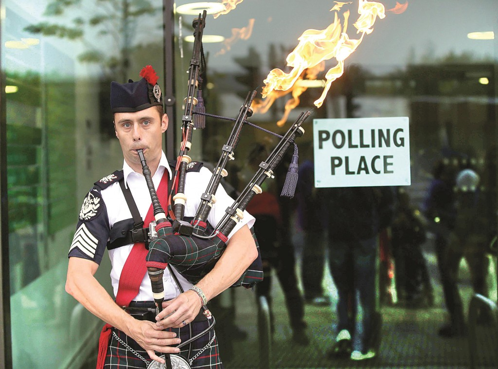 Ryan Randall plays the bagpipes outside a polling station in Edinburgh, Thursday. (REUTERS/Paul Hackett)