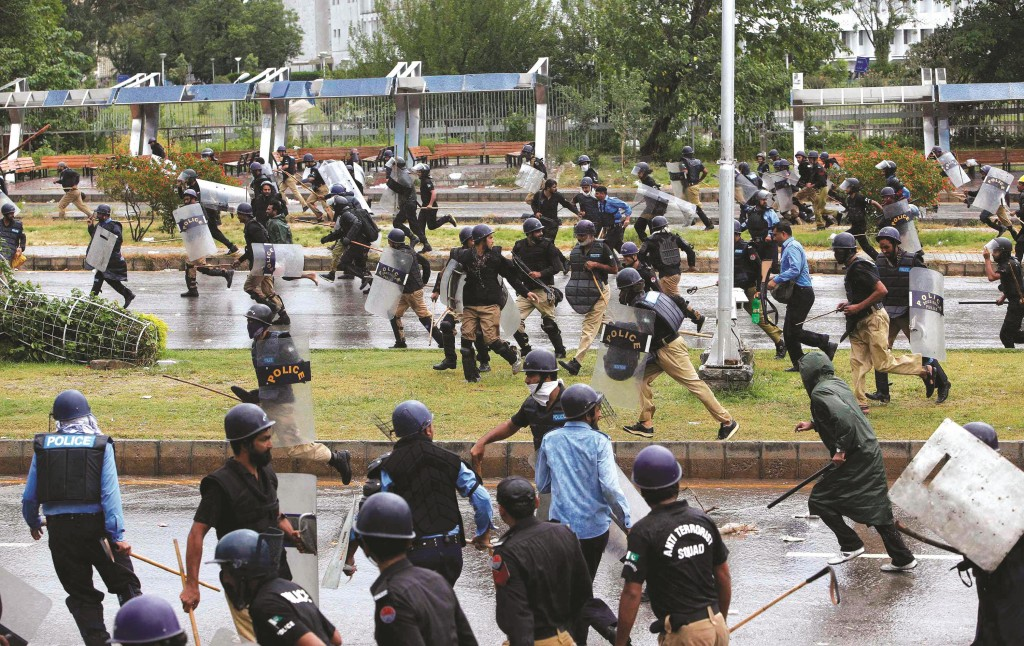 Policemen run away from anti-government protesters during the Revolution March towards the prime minister's house in Islamabad Monday. (REUTERS/Akhtar Soomro)