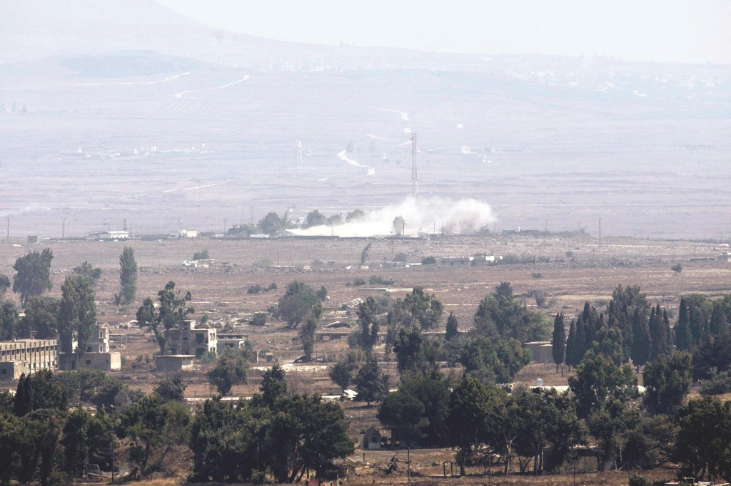 Smoke rises at a U.N. base in Syria near a border fence with Israel on the Golan Heights on Monday. (REUTERS/Baz Ratner)