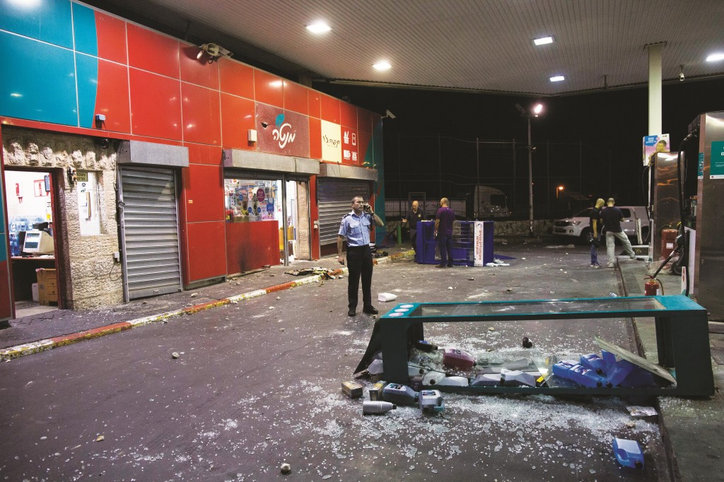 Police inspecting the gas station in French Hill where Arabs rioted earlier this week. (Yonatan Sindel/Flash90)