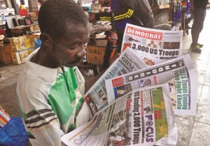 A vendor shows news paper headlines commenting on President Obama announcement on sending troops to fight the Ebola virus in Monrovia, Liberia, Wednesday, Sept. 17, 2014.  (AP Photo/Abbas Dulleh)