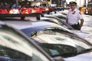 police officer on Wednesday stands in front of a row of police cars parked in Times Square. (AP Photo/Seth Wenig)