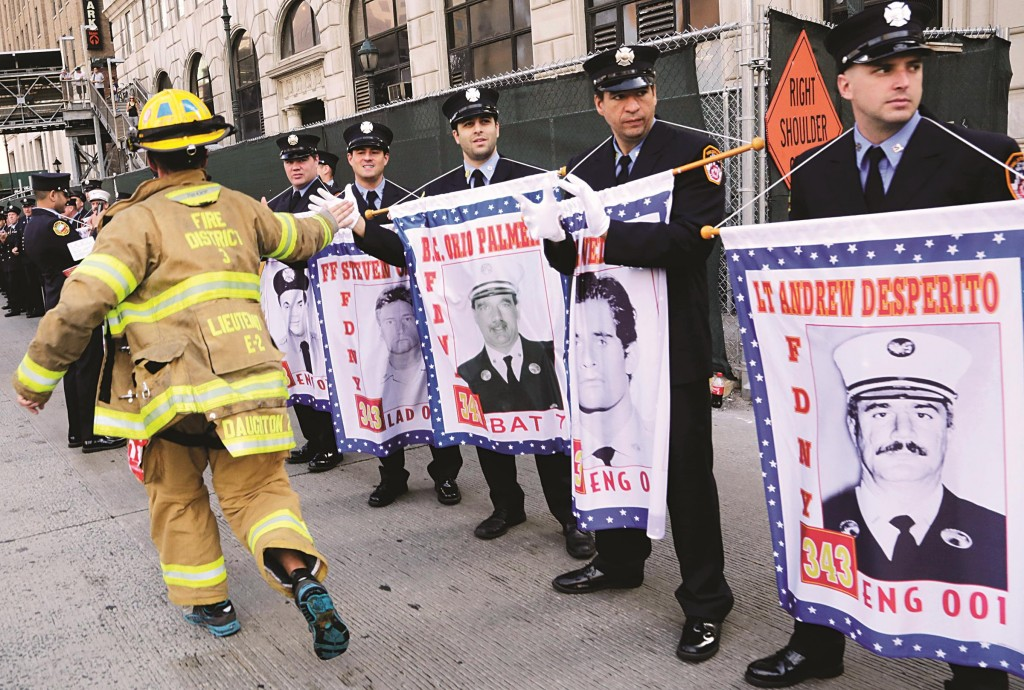 """A firefighter runs past New York firefighters, holding banners honoring their comrades who died on 9/11, during the annual """"Stephen Siller Tunnel to Towers"""" run on Sunday, in New York. The run honors New York firefighter Stephen Siller, who on Sept. 11, 2001, made his way from his Brooklyn firehouse through the Hugh Carey Tunnel, then known as the Brooklyn Battery Tunnel, to the World Trade Center, where he died in the collapse of the towers.  (APPhoto/Mark Lennihan)"""