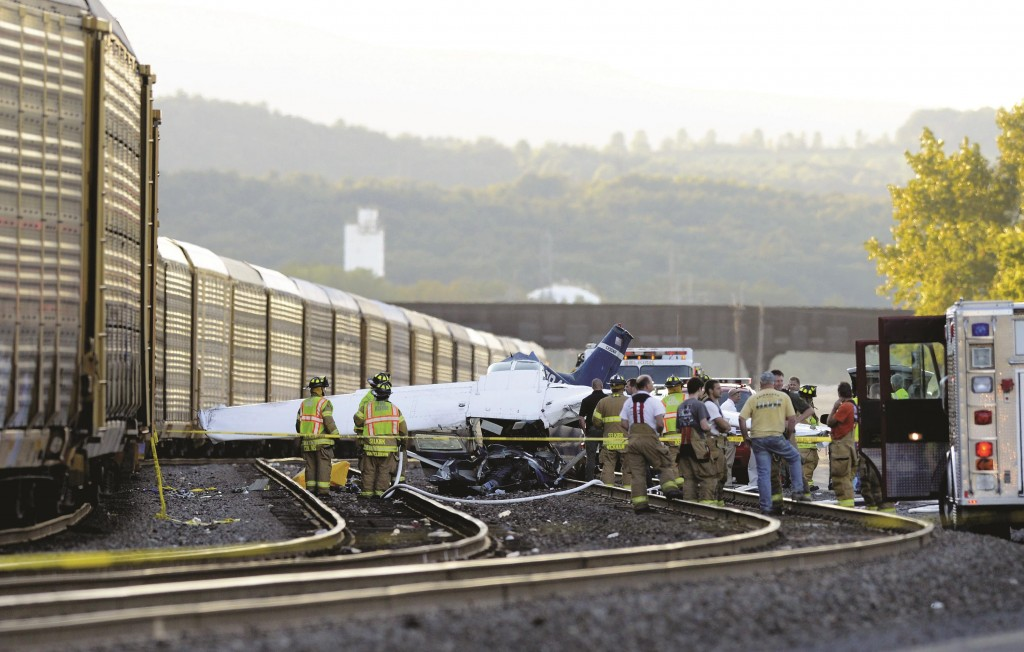 Rescue workers on Monday at the scene where a small plane crashed into a freight train carrying automobiles near Albany. Both flyers, an instructer and his student, were killed. (AP Photo/Times Union, Will Waldsron)