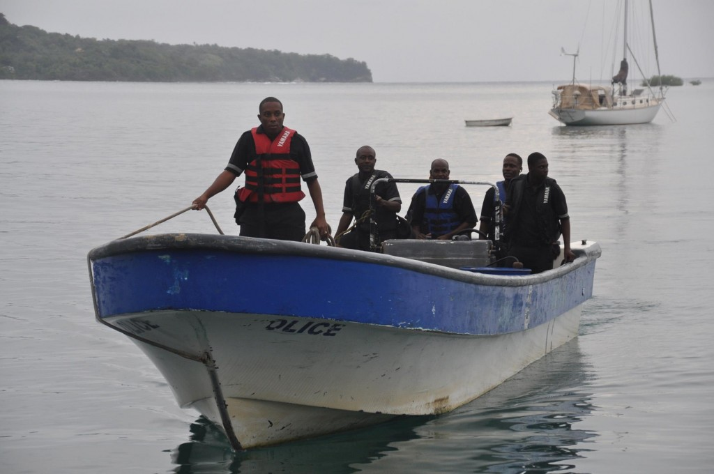 Jamaican Marine Police return Friday to port after a fruitless search for the plane carrying Larry (inset) and Jane Glazer that crashed into the ocean. (AP Photo/Everard Owen)