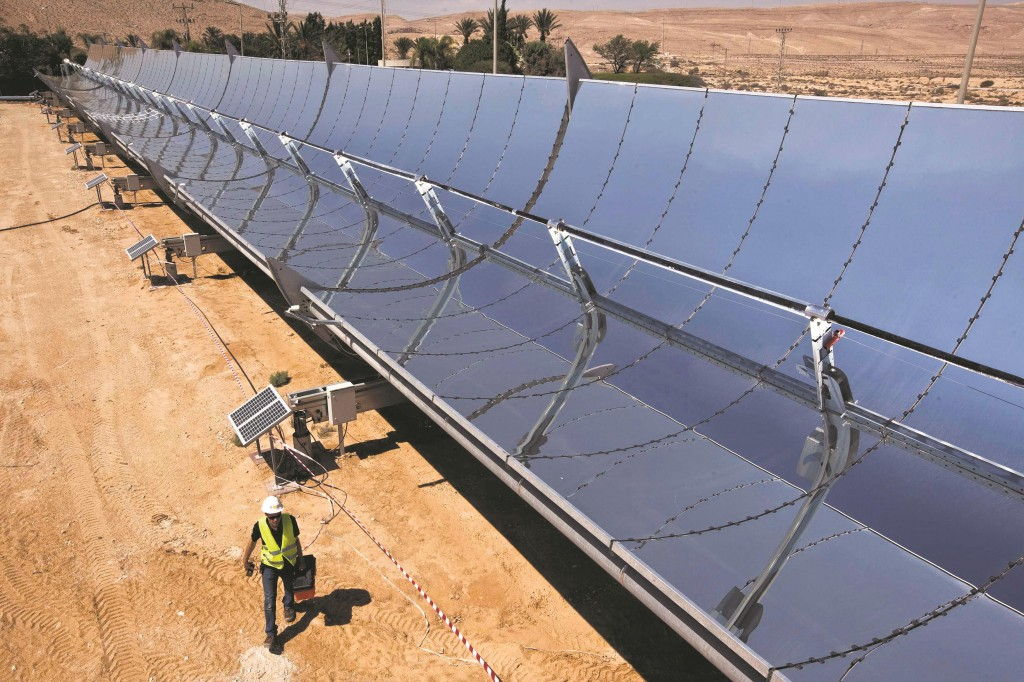 A worker walks next to parabolic mirrors tracking the sun at Brenmiller's research site in the Negev desert. An Israeli solar power company, Brenmiller Energy, says it has developed a new, more efficient way to store heat from the sun that could give a boost to the thermal solar power industry by enabling plants to run at full capacity night and day. By next year, company founder Avi Brenmiller said he will have a 1.5 megawatt (MW), 15-acre site in the Negev desert connected to Israel's national grid, and a number of 10- to 20-MW pilots abroad are expected to follow, which will produce electricity at a price which competes with power from fossil-fueled plants. (REUTERS/ Nir Elias)