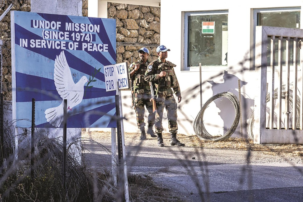 United Nations Disengagement Observer Force (UNDOF) members stand guard at the entrance to the U.N. headquarters in the demilitarized zone, near the Quneitra border crossing in the Israeli Golan Heights. (JACK GUEZ/AFP/Getty Images)