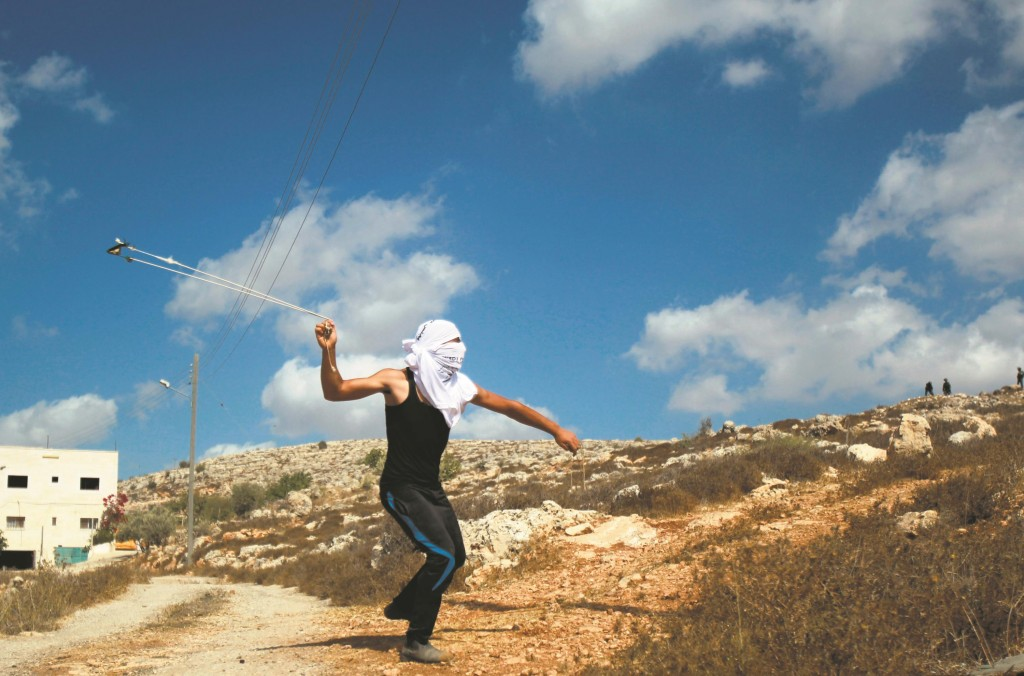 A Palestinian protester uses a sling to throw stones towards Israeli soldiers during a demonstration on Friday near the village of Wadi Fukin, between the cities of Beis Lechem and (Chevron. MUSA AL-SHAER/AFP/Getty Images)