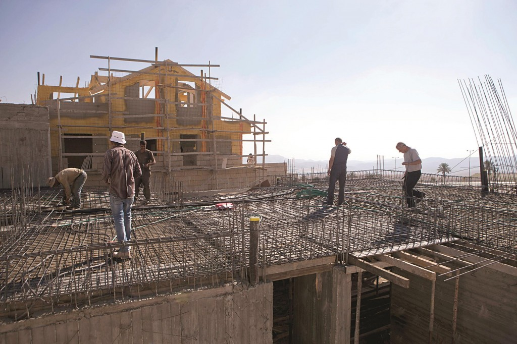 Palestinian laborers working at a construction site in Maalei Adumim, near Yerushalayim, Tuesday. (AP Photo/Dan Balilty)