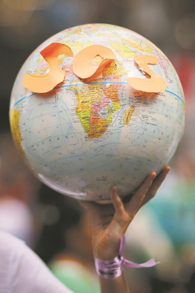 A protester holds a globe with the letters SOS while taking part in a march against climate change in New York. (REUTERS/Eduardo Munoz)