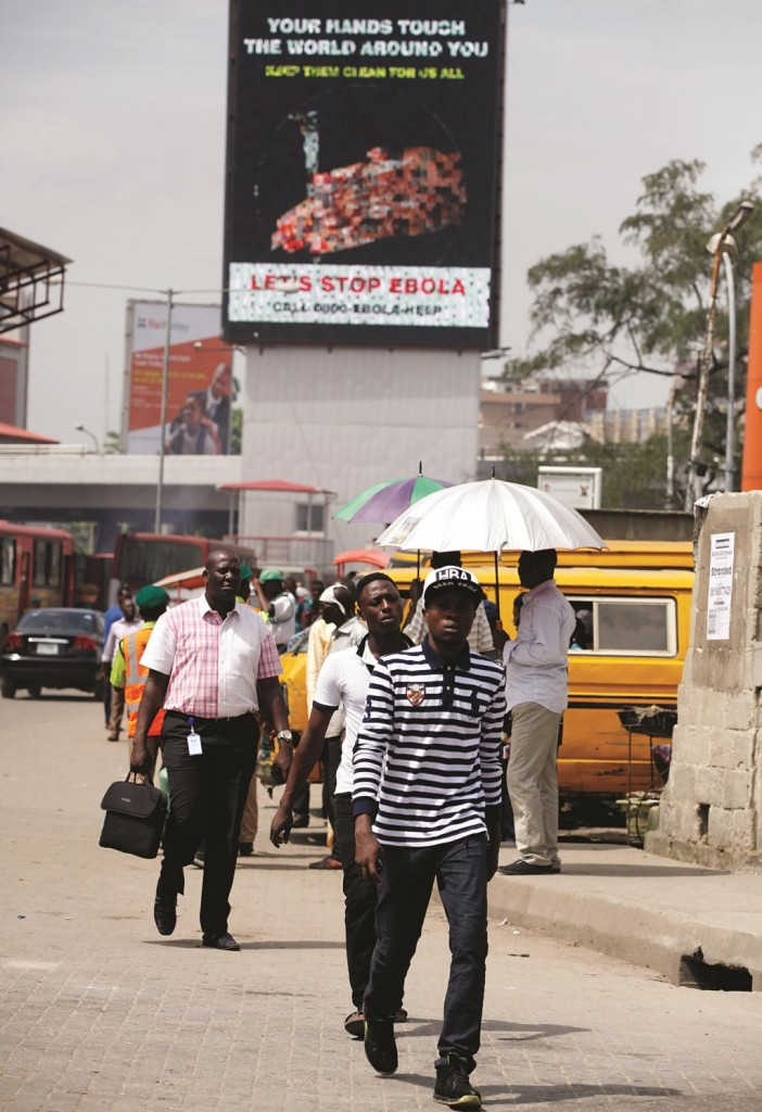 People walk past a giant electric board warning people on Ebola virus near a hospital where Liberian-American Patrick Sawyer died in Lagos, Nigeria, Monday. On Monday, the World Health Organization announced a rare victory in the months-long battle against the killer disease, declaring Nigeria is Ebola-free.  (AP Photo/Sunday Alamba)