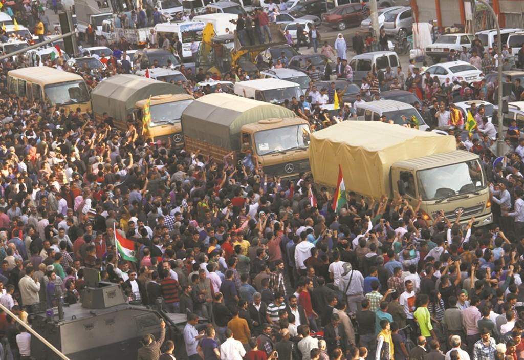 People cheer a group of Iraqi Kurdish peshmerga troops as they arrive in Mardin, southeastern Turkey, Wednesday. (AP photo)