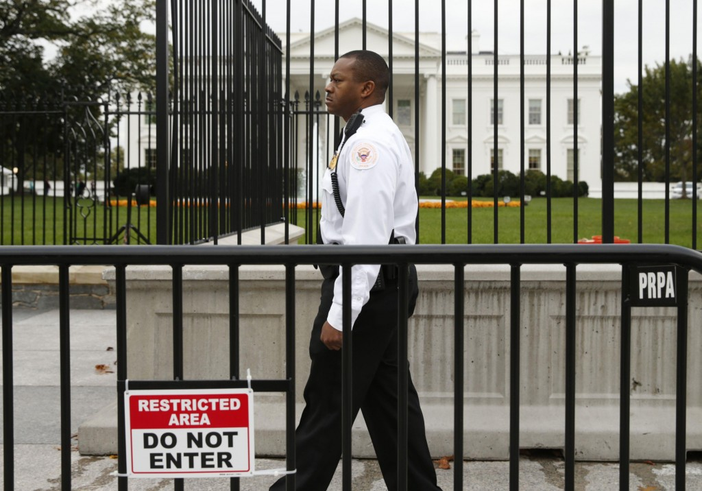 A member of the U.S. Secret Service patrols in front of the North Lawn fence of the White House in Washington Thursday. (REUTERS/Kevin Lamarque)