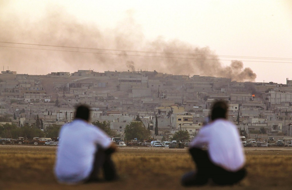Turkish Kurds sit on the outskirts of Suruc, on the Turkey-Syria border, as they watch smoke rising from a fire following an airstrike in Kobani, Syria, where the fighting between terrorists of the Islamic State group and Kurdish forces intensified on Tuesday. (AP Photo/Lefteris Pitarakis)