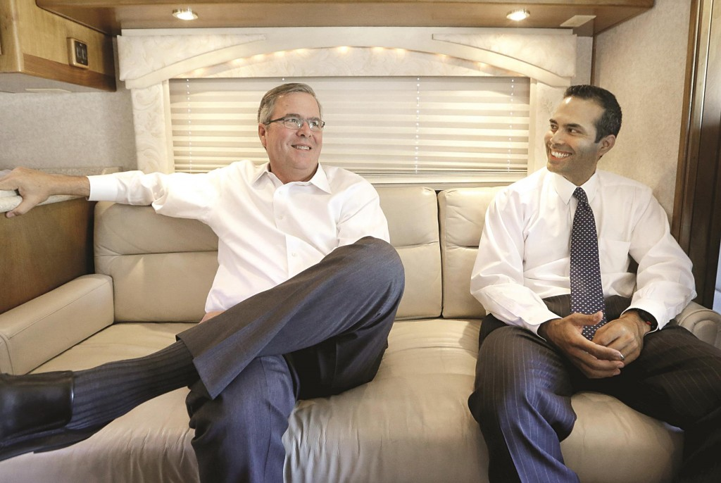 Former Florida Gov. Jeb Bush, left, and his his son George P. Bush smile as they sit on a campaign bus during a recent appearance in Abilene, Texas. (AP Photo/LM Otero)