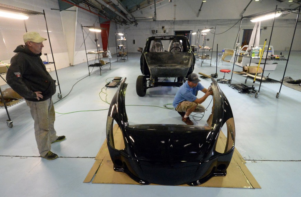 Ben Agnew, right, and Barry Robinson, left, work on the body of the EV Fleet's 2015 Condor prototypes at ReVenture Park in Charlotte, N.C. (Jeff Willhelm/Charlotte Observer/MCT)