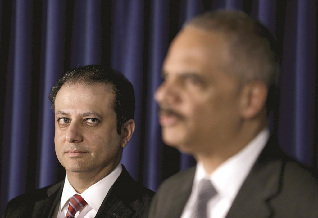 U.S. Attorney for the Southern District of New York Preet Bharara, left, looks on as Attorney General Eric Holder speaks. (AP Photo/Seth Wenig)
