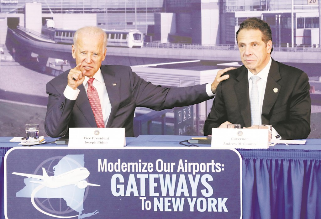Vice President Joe Biden (L) with Gov. Andrew Cuomo speaks Monday in a hangar near LaGuardia Airport about a plan to modernize the area's airports. (AP Photo/Richard Drew)
