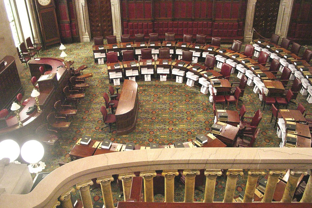 The New York State Senate chamber, with stacks of paper bills on each desk.