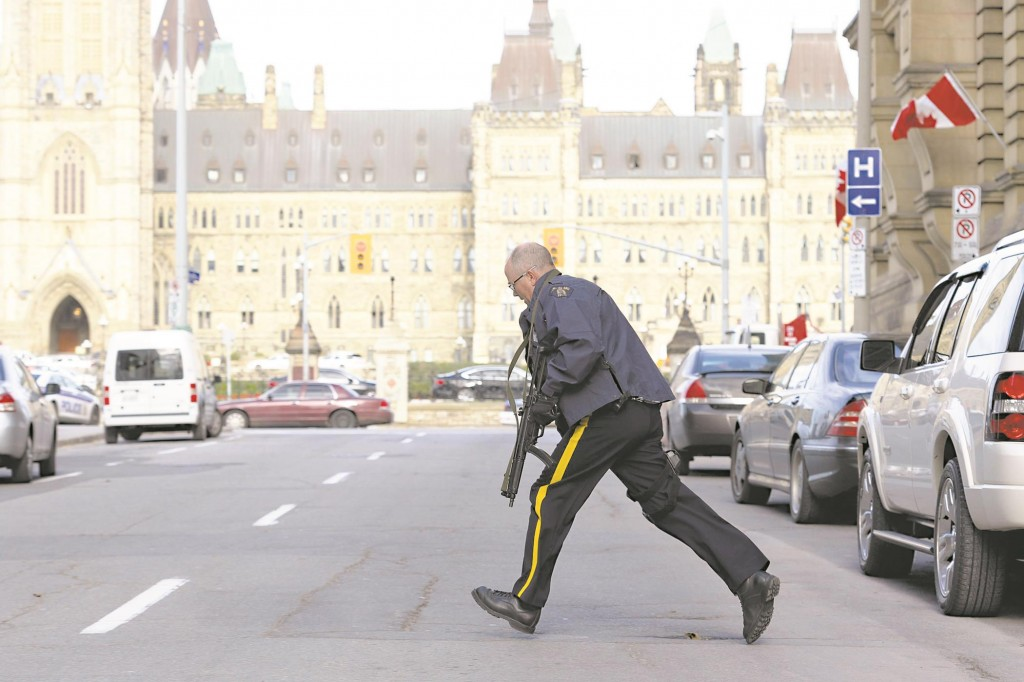 A police officer races across a street on Parliament Hilll following a shooting incident in Ottawa Wednesday. (REUTERS/Chris Wattie)
