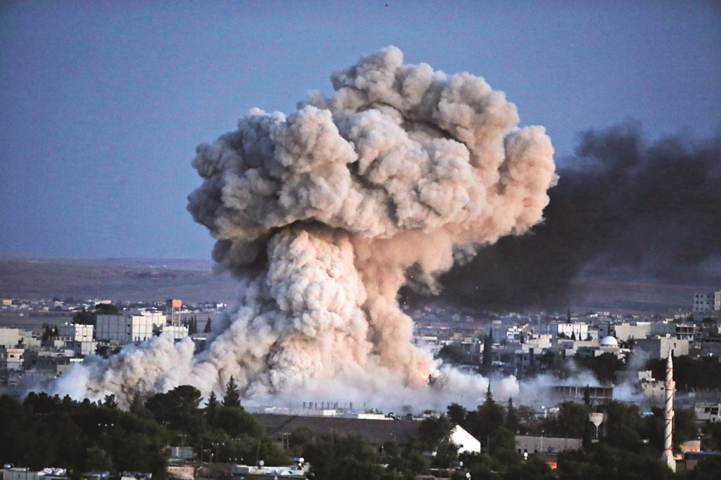 Thick smoke from an airstrike by the U.S.-led coalition forces rises in Kobani, Syria, as seen from a hilltop on the outskirts of Suruc, at the Turkey-Syria border, Monday. (AP Photo/Lefteris Pitarakis)