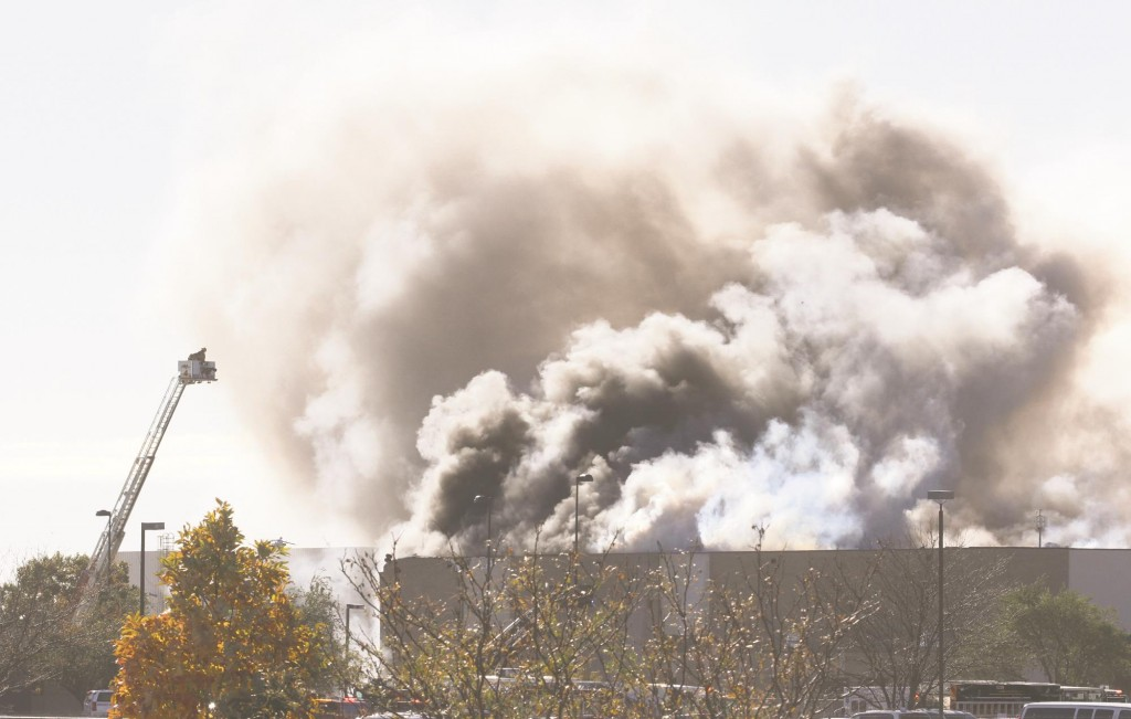 Smoke billows from a building at Mid-Continent Airport in Wichita, Kan., Thursday, shortly after a small plane crashed into the building killing several people, including the pilot.  (AP Photo/The Wichita Eagle, Brian Corn)