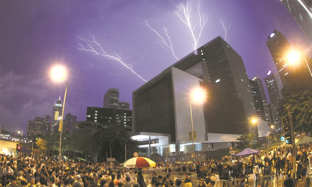Lightning is seen during a rally near a government office in Hong Kong, Friday.  (AP Photo/Apple Daily)