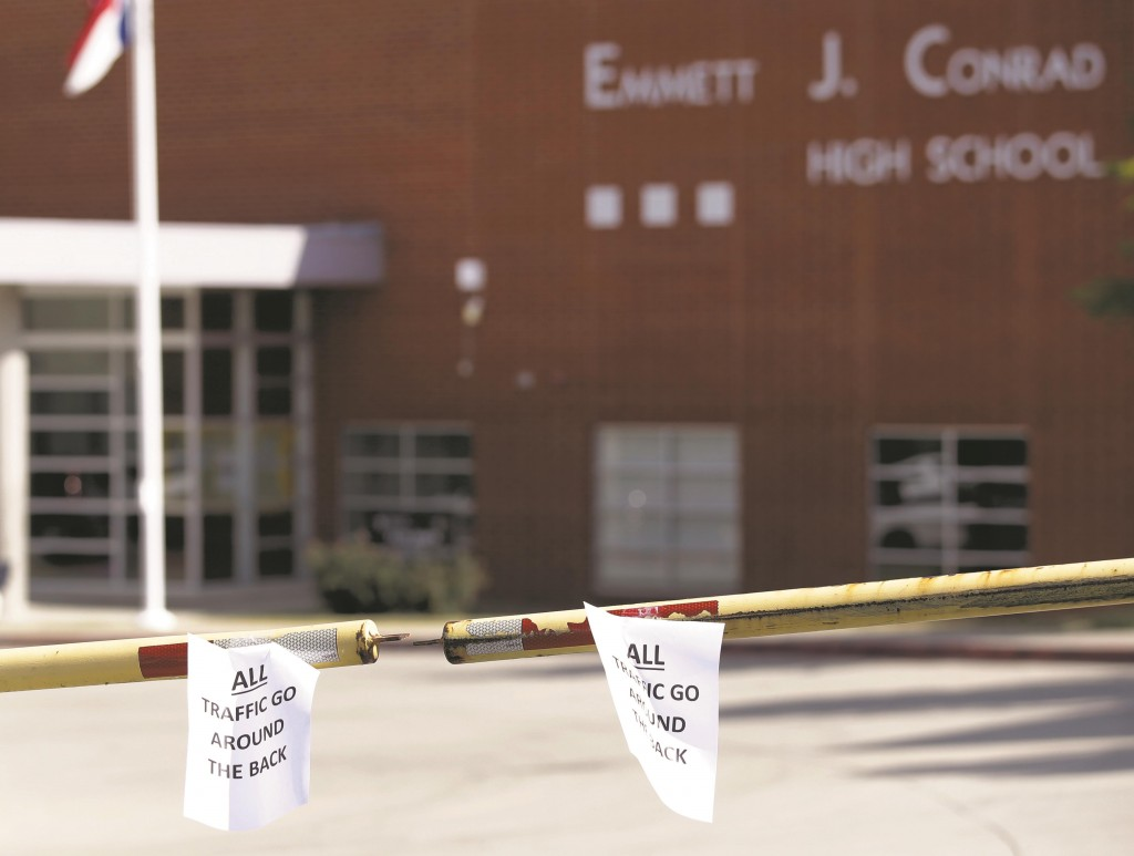 """Signs taped to a closed-off driveway in front of Emmett J. Conrad High School read, """"All Traffic Go Around Back."""" Wednesday, in Dallas. Authorities say five students who had contact with a man diagnosed with Ebola in Dallas are being monitored but are showing no symptoms of the disease.  (AP Photo/Tony Gutierrez)"""