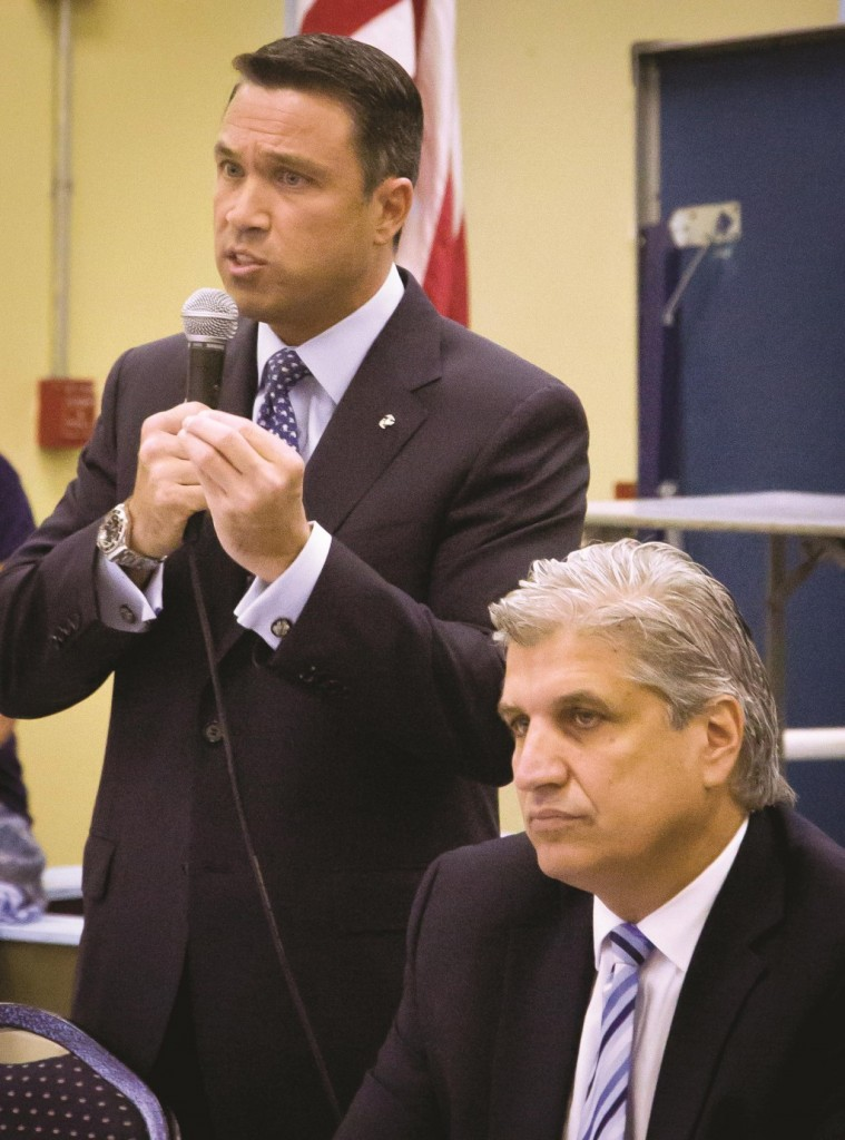 GOP Rep. Michael Grimm on Wednesday stands next to his Democratic challenger Domenic Recchia as he speaks at a candidates forum in Brooklyn. (AP Photo/Bebeto Matthews)