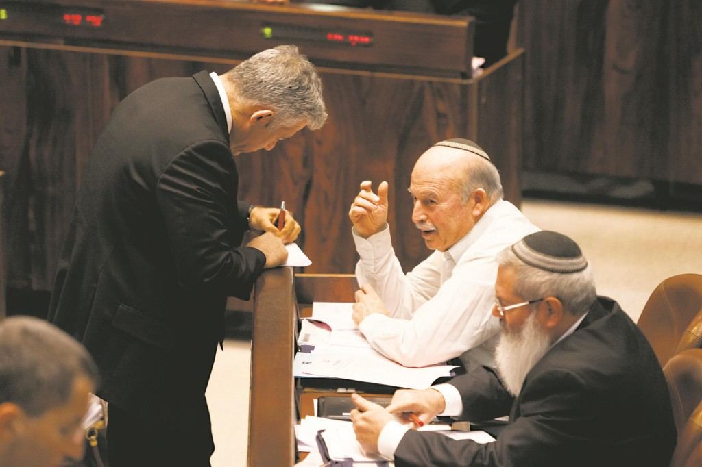 Finance Minister Yair Lapid (standing, L) with Chairman of the Finance Committe Nissan Slomiansky (seated, 2nd R) sorting matters out in the Knesset plenum. (Flash 90)