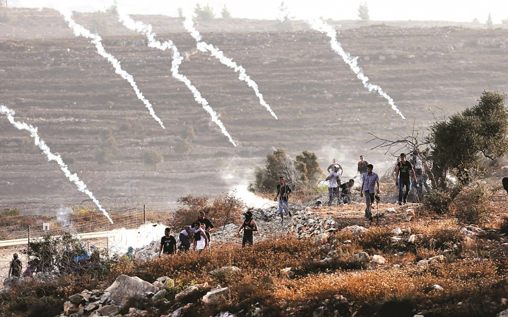 Palestinian protesters gather on a hill as Israeli security forces (unseen) fire tear gas during clashes close to the Israeli Ofer military prison, near Betunia on Friday, following a protest after Israeli authorities restricted access to Har Habayis.  (ABBAS MOMANI/AFP/Getty Images)