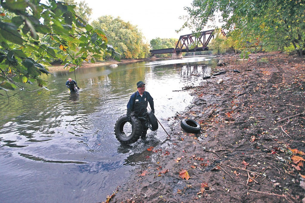 Mike Ramadani on Monday removes tires from the Passaic River as part of a monthlong effort to clean up the area. About 1,000 tires have been removed. (AP Photo/The Record, Kevin R. Wexler)