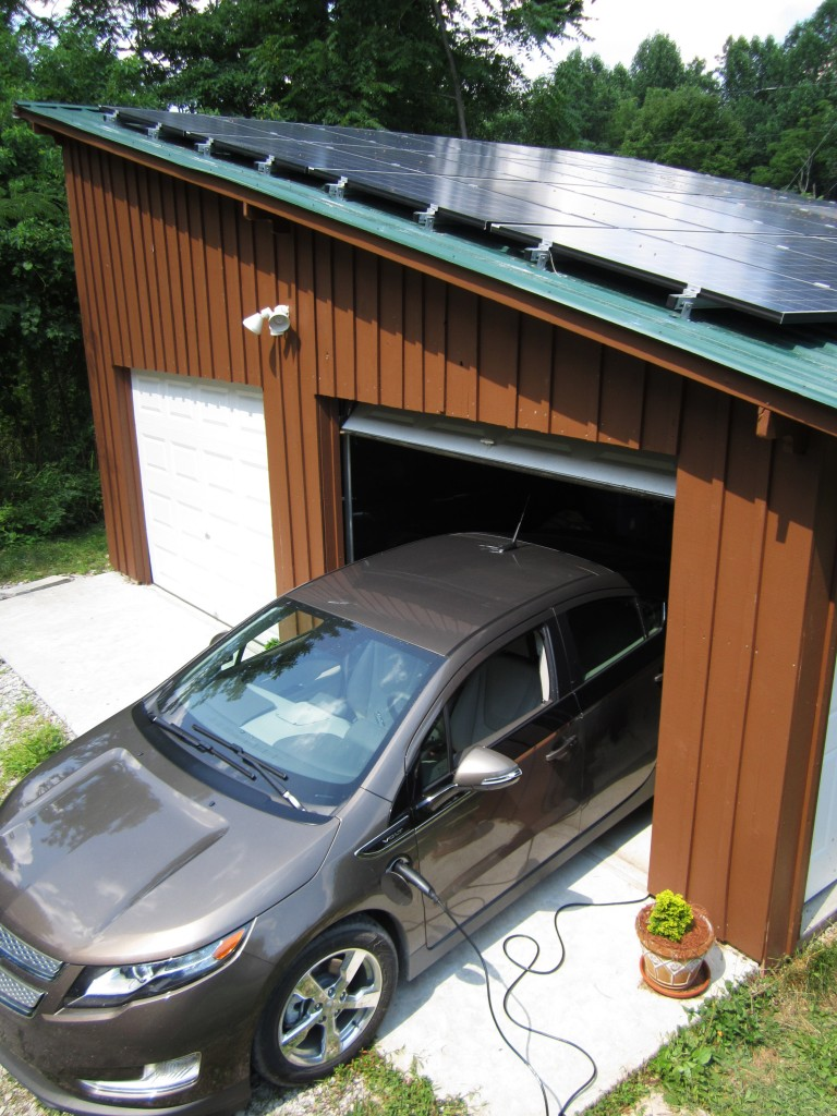 This July 2014 photo, provided by Samuel Avery, shows a 2014 Chevy Volt plug-in in Hart County, Ky. Avery, who is a professional solar installer, built both the garage and panel installation. A growing number of electric-vehicle owners are powering their cars with solar energy from panels on their homes. (AP Photo/Samuel Avery)